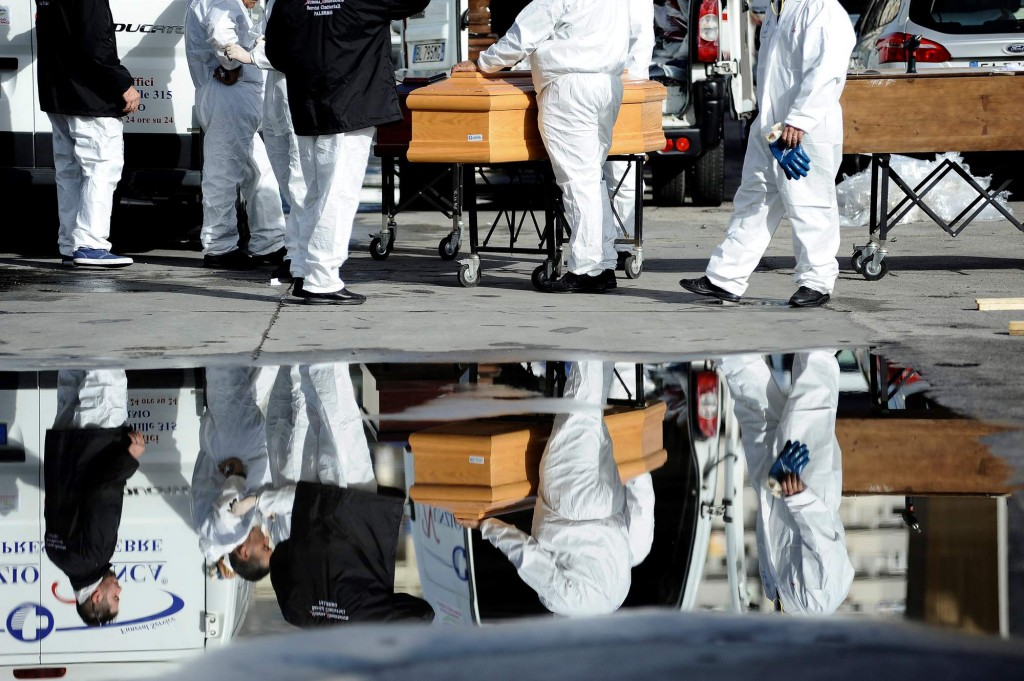 Staff members prepare coffins to be used to contain the bodies of dead migrants in the Sicilian harbour of Palermo