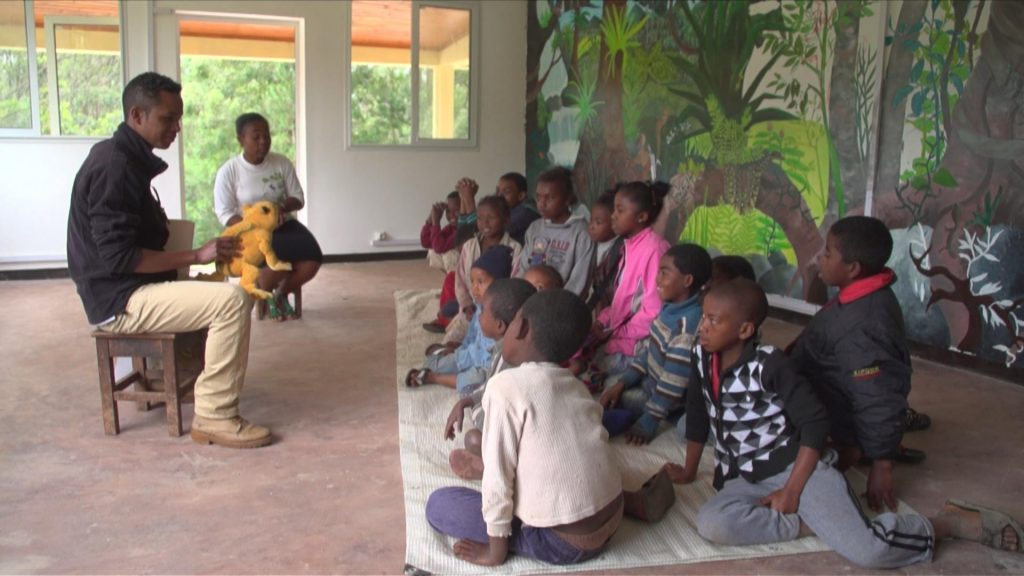 Justin teaching children about the animals in the forest. Mitsinjo holds community sensitization programs to stress the importance of forest conservation.