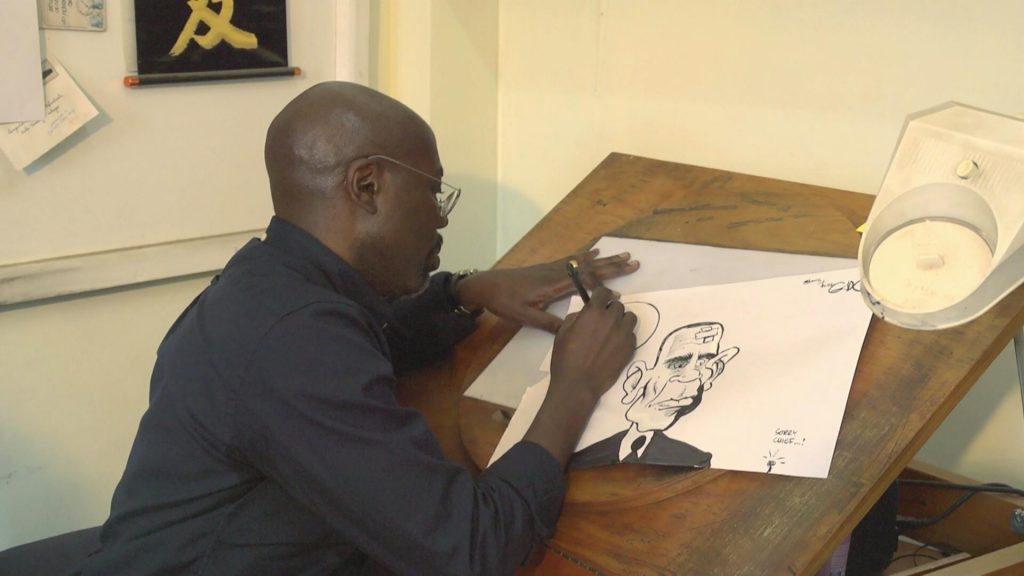 Godfrey Mwampembwa, popularly known as Gado, drawing a cartoon for the XYZ show. He is a professional cartoonist.