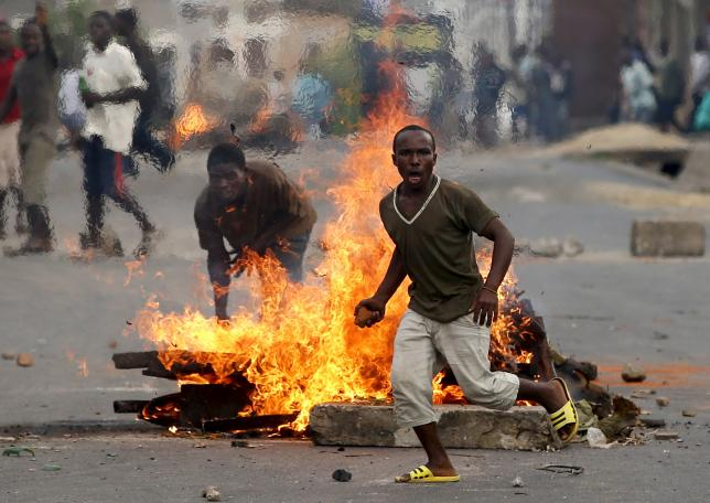 A protester runs in front of a burning barricade during a protest against Burundi President Pierre