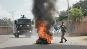 A Burundian army soldier pours water on a burning-tyre roadblock erected by opposition protesters