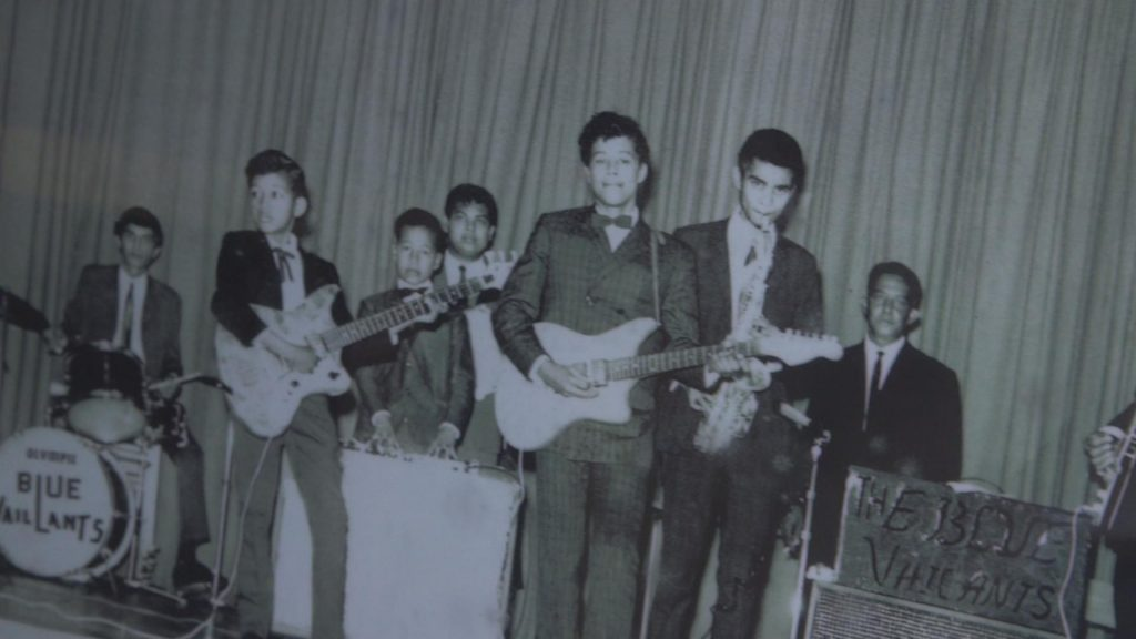 Young Philippe with his five brothers performing. His dad (sitting in a black suit) had founded the Blue Valiants band.