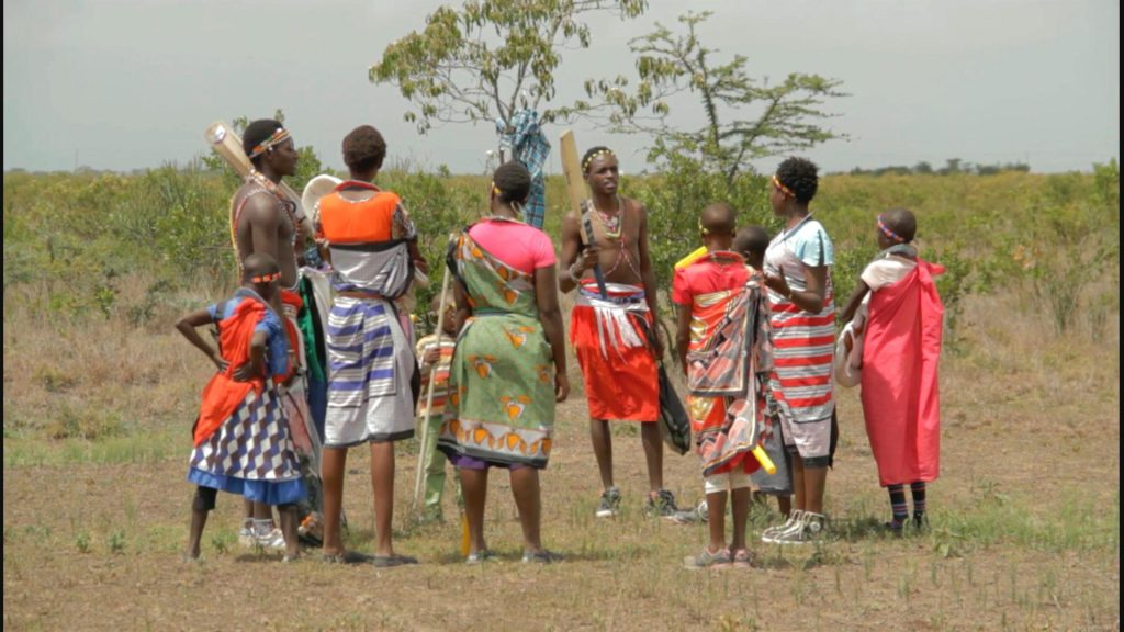 Sonyanga and Christopher talking to the girls in their village. They use cricket as a tool to eradicate early marriages and female genital mutilation for the Maasai girls.