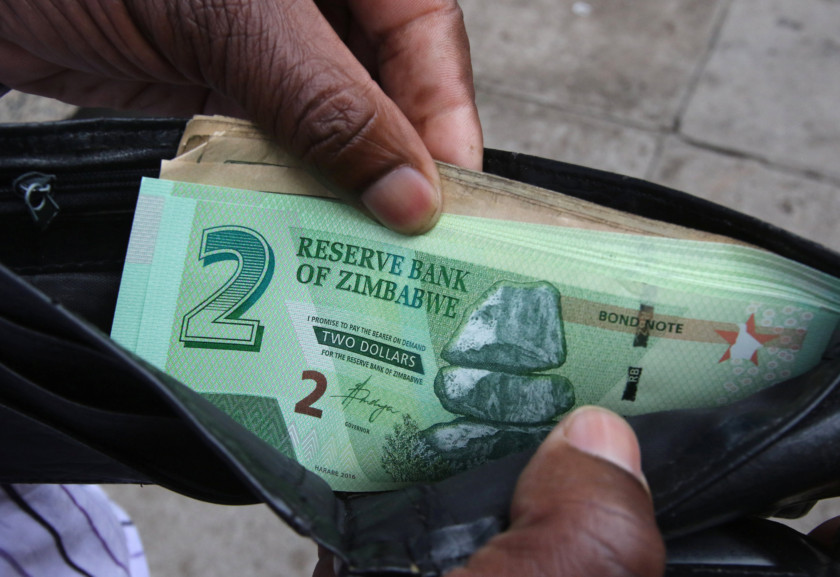 A Zimbabwean man shows off new bond notes outside a bank in Harare on November 28, 2016. Picture: Philimon Bulawayo/Reuters