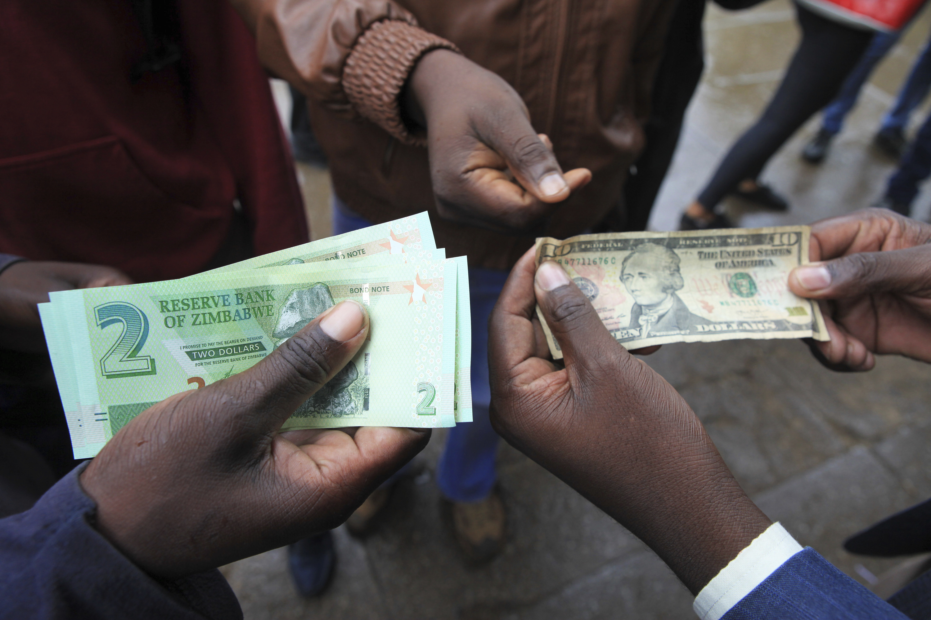 Zimbabweans compare the new note with the US dollar note following the introduction of new notes by the Reserve Bank of Zimbabwe in Harare, Monday, Nov, 28, 2016. The Southern African nation has rolled out a new currency for the first time since 2009 in hopes of easing biting shortages of the US dollar. Banks across the country started issuing the new currency called bond notes, Monday. (AP Photo/Tsvangirayi Mukwazhi)