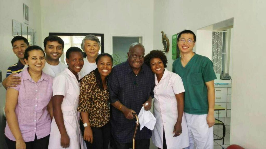 Dr. Gao with his employees and the former president of Zambia, Kenneth Kaunda