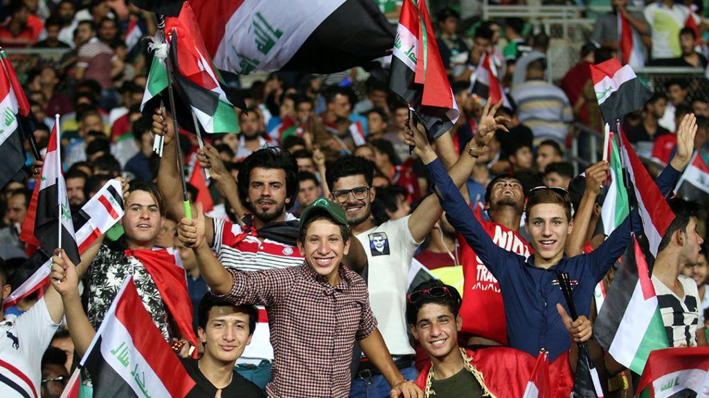 Supporters of the Iraqi national team wave their national flag during the international friendly football match between Iraq and Jordan at Basra Sports City in Basra on June 1, 2017.  / AFP PHOTO / HAIDAR MOHAMMED ALI