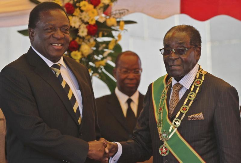 FILE PHOTO: President Robert Mugabe (R) greets Vice President Emmerson Mnangagwa as he arrives for  Zimbabwe's Heroes Day commemorations in Harare, August 10, 2015. REUTERS/Philimon Bulawayo